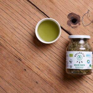 Bio Tee Wilde Mate, auf hölzernem Hintergrund mit Mate im Teeei, Tee im Mehrwegglas