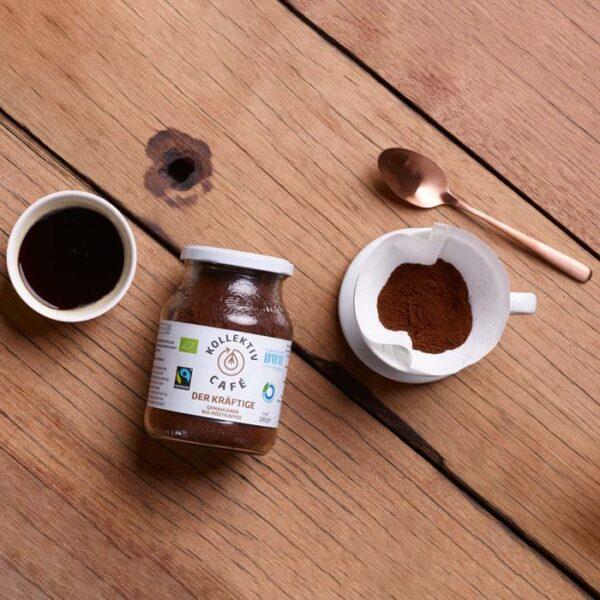 Fairtrade Bio Kaffee der Kräftige, danben Kaffeepulver in Kaffeefilter in Tasse, ein Löffel und eine Tasse Kaffee.