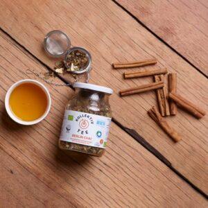 Bio Tee Berlin Chai, CO2 Neutral produziert, im Mehrwegglas. Mit Zimstangen gehäuft, darüber ein Teeei halb gefüllt, links davon eine Tasse Tee.