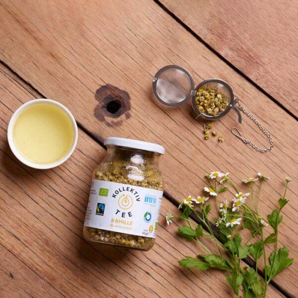 Bio Tee Kamille, CO2 Neutral produziert im Mehrwegglas. Mit einem Strauch Kamille, einem Teeei halb gefüllt und einer Tasse Tee.