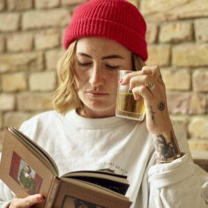 Frau mit weißem Pullover, roter Mütze, kurzen blonden Haaren, liest Buch und hält durchsichtiges Glas mit Bio Tee.