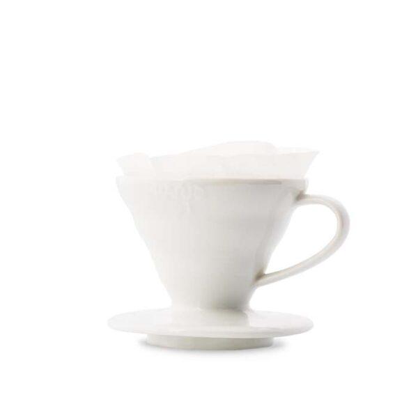 Handfilter auf Glashalter mit Kork. Tee wird aus einer Teekanne in die Tasse gekippt. Im Hintergrund: graue Couch und Pflanze.