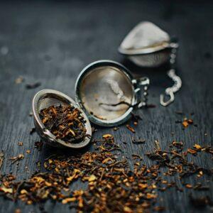 Teeei geöffnet mit Krümeltee, der in Teeei und auf Untergrund verteilt ist. Zweites Teeei verschwommen im Hintergrund.