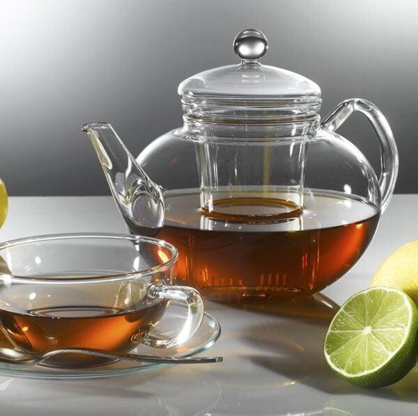 Teekanne mit Deckel und gläserne Tasse gefüllt mit Bio Tee auf Untertasse mit Teelöffel. Rechts eine halbe Limette.