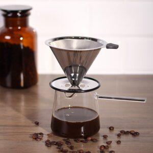 Handfilter auf Glaskanne mit Kaffee gefüllt. Davor Kaffeebohnen. Im Hintergrund ein verschwommenes Gefäß mit Kaffeebohnen.