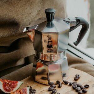 Bialetti Espressokocher aus Aluminium auf Holzbrett mit verteilten Kaffeebohnen und aufgeschnittener Feige.