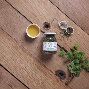 Bio Tee Pfefferminze, CO2 Neutral produziert, mit einem Strauch Pfefferminze, einem Teeei halb gefüllt und einer Tasse Tee.