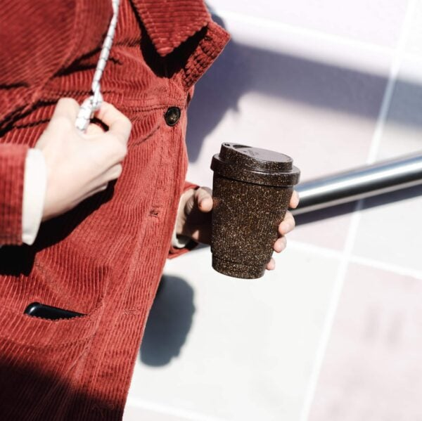 To Go-Becher aus Kaffeesatz. Person mit roter Kordjacke, weißem Rucksackgriff und Handy aus Jackentasche herausschauend.