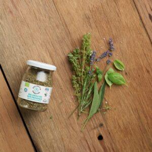 Bio Gewürz Kräuter de Provance im Mehrwegglas, auf hölzernen Hintergrund mit Basilikum, Lavendel, Rosmarin und Oregano.