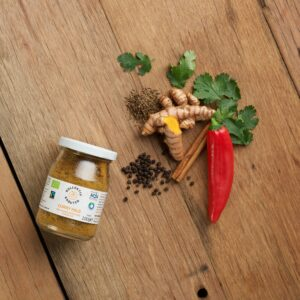Bio Gewürz Curry Mild im Mehrwegglas, auf hölzernen Hintergrund mit Pfefferkörner, Zimtstange, Chilischote, Ingwar, Petersilie und Kümmel.