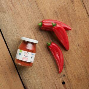 Bio Gewürz edelsüsse Paprika im Mehrwegglas, auf hölzernen Hintergrund mit drei roten Paprikaschoten.