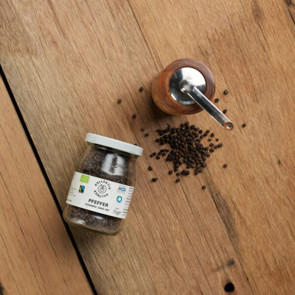 Bio Gewürz schwarzer Pfeffer im Mehrwegglas, auf hölzernen Hintergrund mit einer Pfeffermühle und gehäuften Pfefferkörner.